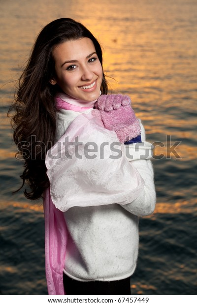 Pretty young woman lifestyle with winter clothing along a seawall on the bay in a downtown scene at sunset.