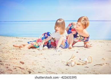 Pretty young woman and little girl are sitting on the seashore