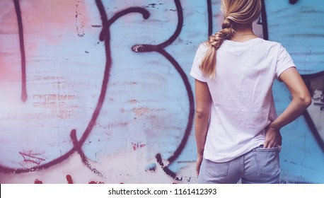 Pretty young woman with a long blond hair standing on a street with the graffiti wall background. Mock up.