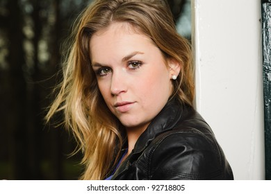 Pretty young woman long blond hair in winter forest wearing black leather jacket and blue shirt