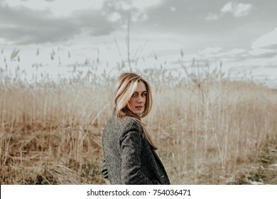 Pretty and young woman with long blonde hair dressed in wool coat looking at camera over her shoulder and smiling. Background bulrush. Autumn. Outdoor. Medium shot