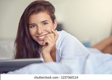 Pretty young woman with long brown hair, laying on stomach in bed with white linens and using tablet pc, smiling at the camera with copy space