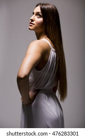 Pretty young woman with long hair in white dress in studio