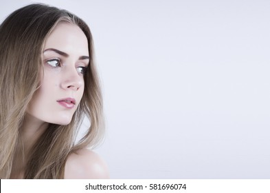 Pretty young woman with long hair on white background looking sideways. Headshot. Studio. Portrait.