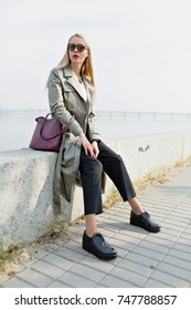 Pretty young woman with long hair in stylish autumn coat enjoying weekend, spending time outside on river background. Attractive young woman with trendy look walking down the street by yellow trees