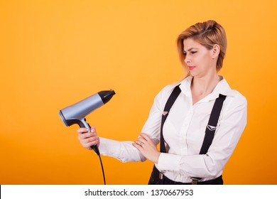 Pretty young woman looking confused at her hair drayer over yellow background. Blue blowdryer. Haicare.