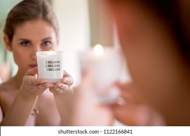 Pretty young woman looking into a mirror holding a candel for her morning ritual