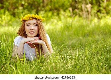 pretty young woman lying on the grass. cute girl with a wreath of dandelions on her head