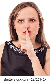 """Pretty young woman making a"""" keep it quiet"""" gesture against white background"""