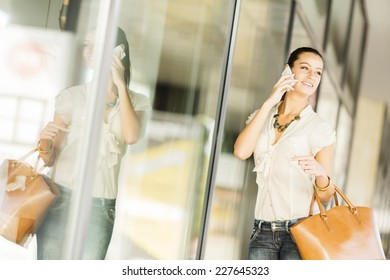 Pretty young woman with mobile phone on the street