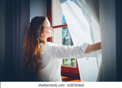 Pretty young woman in modern apartment opening window curtains after wake up