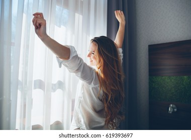 Pretty young woman in modern apartment stretching after wake up