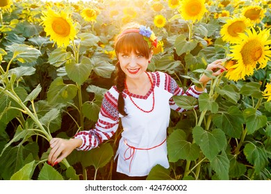 Pretty young woman in national ukrainian blouse embrodery looking to camera on a sunflower field at sunset, backlight.