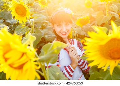 Pretty young woman in national ukrainian blouse embrodery looking to camera on a sunflower plant at sunset, backlight.