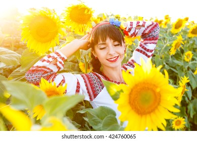 Pretty young woman in national ukrainian blouse embrodery with closrd eyes on a sunflower plant at sunset, backlight.