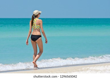 Pretty Young Woman on Vacation taking a leisure walk and enjoying a Beautiful Sunny Day on the Beach.