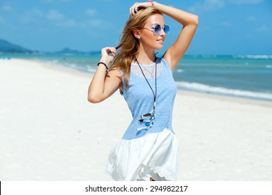 Pretty young woman outdoor closeup portrait posing on the beach blue sky nice weather on tropic island having fun in colorful dress