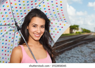 Pretty young woman outdoors with a polka dot umbrella by a railroad track.