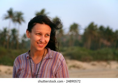 Pretty young woman over green palms on the beach