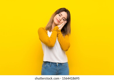 Pretty young woman over isolated yellow wall making sleep gesture in dorable expression