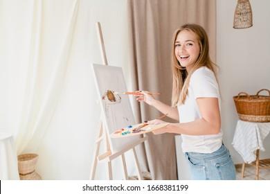hübsche junge Frau, die ein Bild auf Leinwand in der Studiowerkstatt malte
