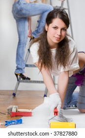 Pretty young woman with painting roller