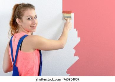 pretty young woman painting the wall pink color