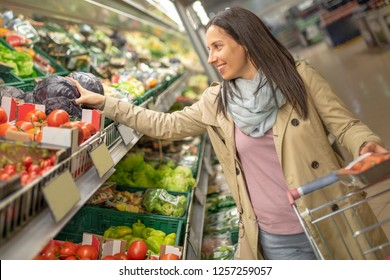 Pretty young woman picking up, choosing green leafy vegetables in grocery store. Attractive woman shopping in supermarket. Shopping woman buying healthy food. Healthy lifestyle concept.