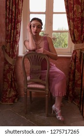 Pretty young woman in pink 1920s Gatsby flapper dress and headband sitting in antique interior