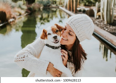 Pretty young woman playing with her adorable dog Jack Rusell in a park surrounded by cactus and a small pond. Adorable sunny autumn day. Lifestyle.