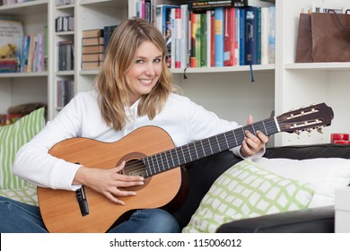 Pretty young woman plays guitar on the couch at home