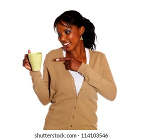 Pretty young woman pointing a mug against white background