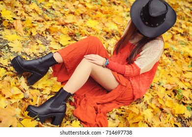Pretty young woman posing in autumn park, leather hat and tractor sole shoes, no face
