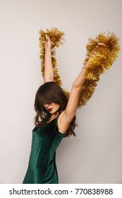 Pretty young woman posing with golden tinsel Christmas decoration.