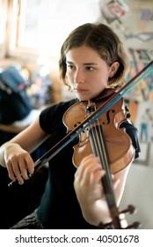 Pretty young woman practicing violin. Available light, selective focus, focus sharpest on eyes.
