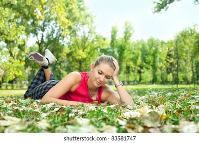 pretty young woman reading book in park