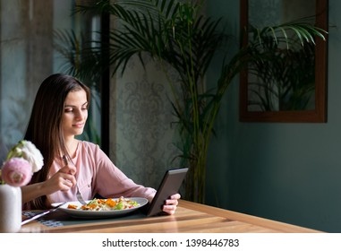 Pretty young woman reading e-book from electronic reader or tablet while having lunch break at the restaurant