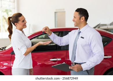 pretty young woman receiving car key from dealership
