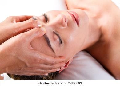 pretty young woman receiving a head massage in beauty salon