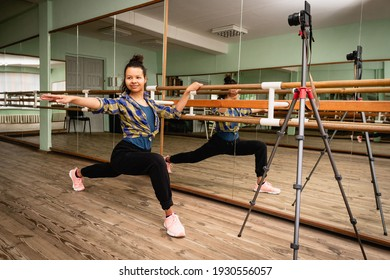 Pretty young woman is recording a fitness lesson. She shows stretching exercise