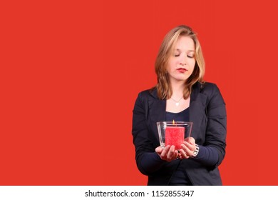 Pretty young woman with red candle in front of red backdrop