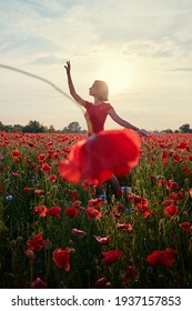 Pretty young woman in red dress dancing like ballerina in the poppy flowers meadow.