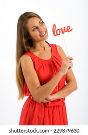 Pretty young woman in a red dress standing holding a the word - Love - dreaming of her sweetheart on Valentines Day looking into the air with a happy smile, isolated on white