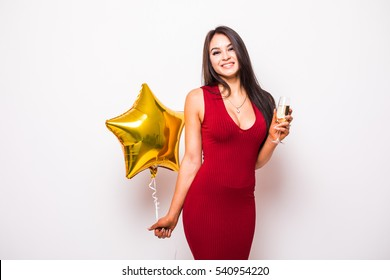 f2c9a948265f Pretty young woman in red dress with gold star shaped balloon smiling and drinking  champagne over