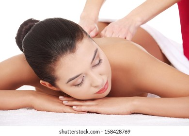 Pretty young woman relaxing beeing massaged in spa saloon