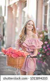 Pretty young woman is riding on a white bicycle in the city. She is smiling and wearing a pink off shoulder dress. On her bike is basket with pink roses.