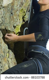 Pretty Young Woman Rock Climbing a cliff with ropes