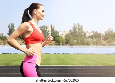 Pretty young woman running at stadium