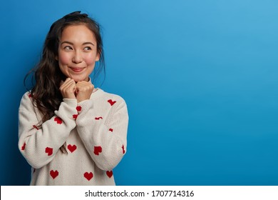 Pretty young woman sees something wonderful, tempting to buy, keeps hands under chin, looks with smile aside, remembers pleasant moment, dressed in casual jumper, poses against blue background