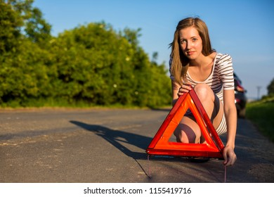 Pretty, young woman setting the safety triangle on the roadside after her car has broken down